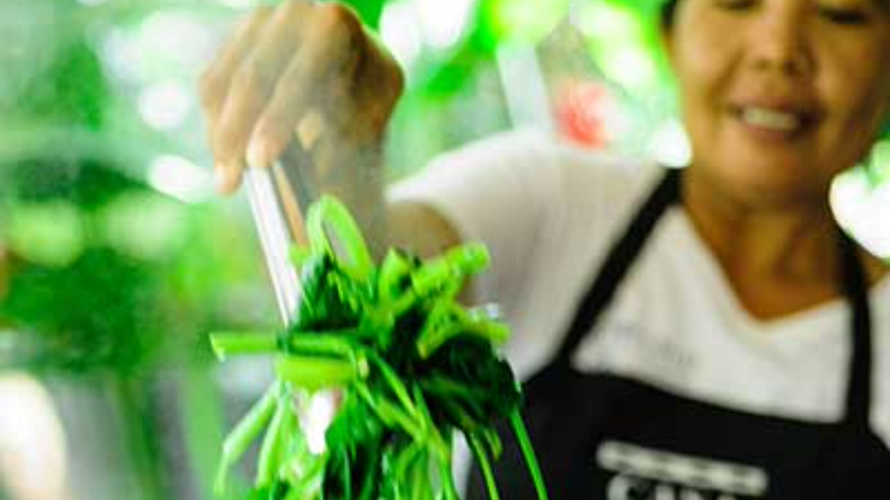 Balinese woman preparing Asian spinach